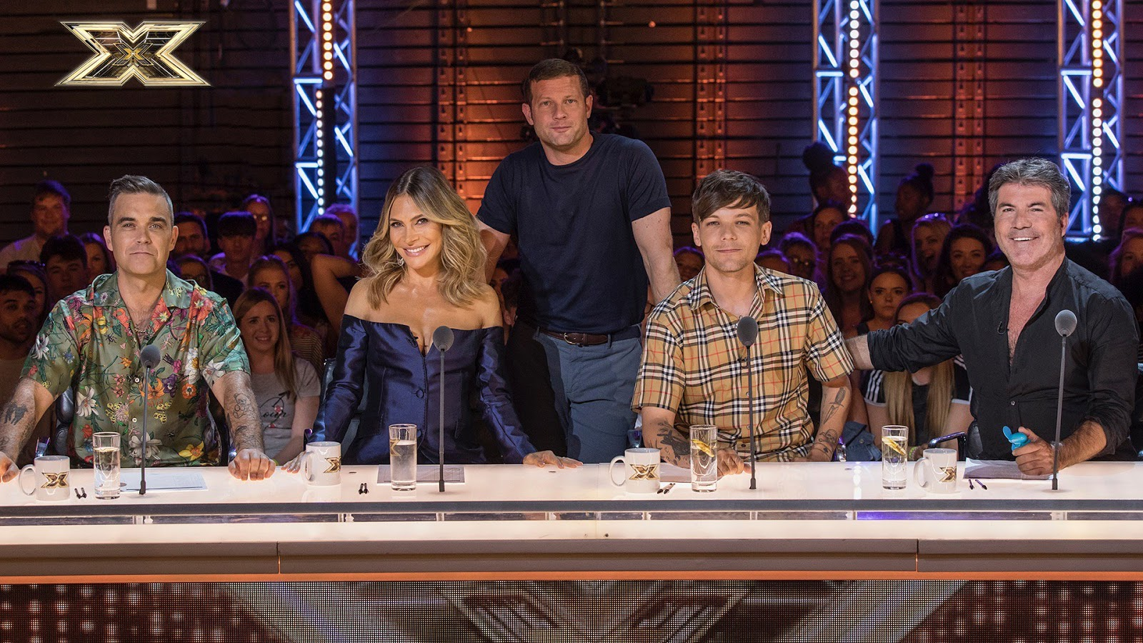 Os jurados Robbie Williams, Ayda Field, Louis Tomlinson e Simon Cowell com o apresentador Dermot O'Leary no The X Factor UK 2018, reality show musical. [Imagem: Divulgação/ITV]